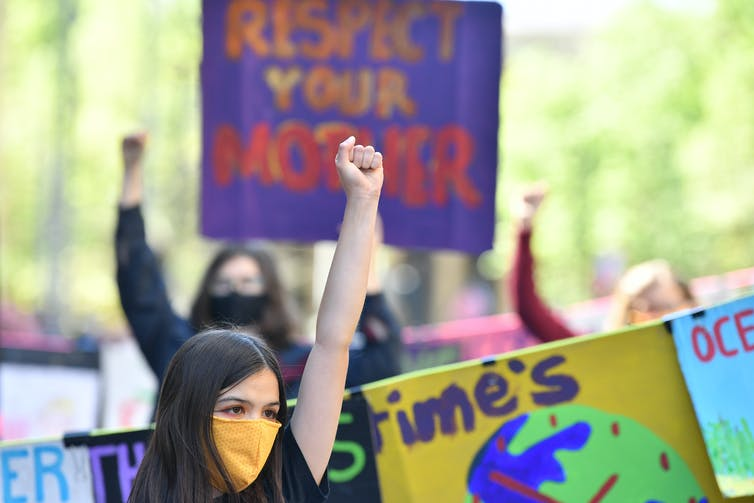 Girl in mask raises fist at climate rally